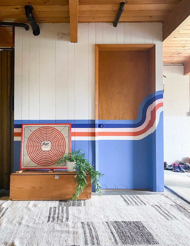The Ledger Flatweave Rug from Revival rugs against a light blue striped mural by Banyan Bridges.